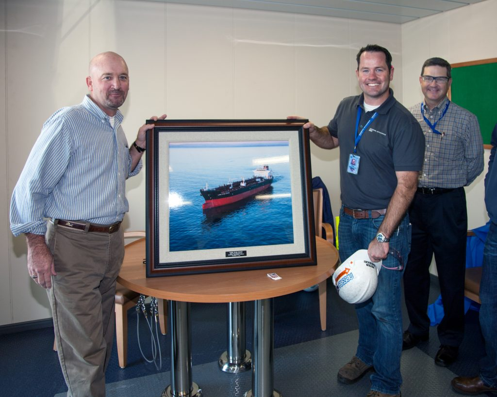 A framed photo of the Lone Star State is presented by Pete Radzicki, program manager for NASSCO's ECO program, to David Farrell, project manager for American Petroleum Tankers. In the background: Kevin Graney, vice president and general manager for General Dynamics NASSCO.